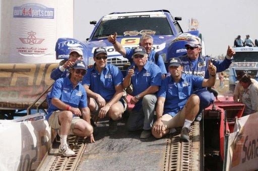Jean-Louis Schlesser (en haut à droite) fête avec son équipe sa victoire dans la 5e édition du rallye Africa Eco Race, le 9 janvier 2012. AFP Mamadou Toure Behan