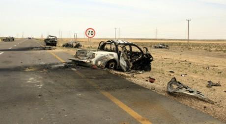 Une voiture incendiée sur la route à Ajdabiyah, Libye, le 16 mars 2011. REUTERS/Ahmed Jadallah