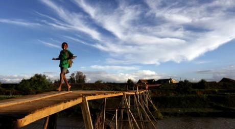 Un écolier malgache traversant un pont dans la campagne d'Antananarivo. Reuters/Siphiwe Sibeko