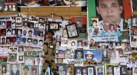 Un rebelle passe devant les photos de Libyens tués lors des affrontements, le 30 avril 2011, à Benghazi. REUTERS/Mohammed Salem