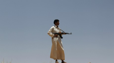 Un rebelle libyen scrute au loin les combats, Al Qawalish, à 100km de la capitaleTripoli, 13 juillet 2011. REUTERS/Ammar Awad