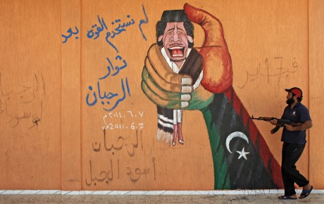 Un rebelle libyen à côté d'un graffiti représentant le colonel Kadhafi par Bob Strong/Reuters