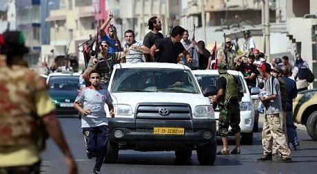 Des combattants rebelles fêtent la prise partielle de Tripoli le lundi 22 août. REUTERS/Bob Strong