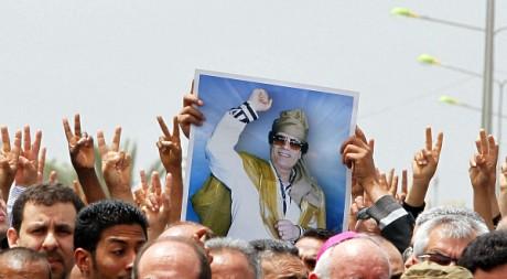 Des partisans de Mouammar Kadhafi brandissent son portrait à Tripoli le 2 mai 2011. REUTERS/Louafi Larbi