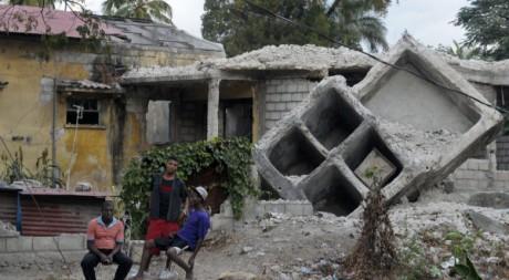 Des Haïtiens devant une maison détruite par le séisme, janvier 2010 © REUTERS/Swoan Parker