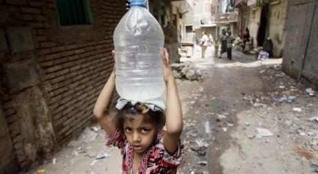 Une jeune fille porte une bombonne d'eau à Manshiyet Nasser en Egypte le 18 mai 2010.Reuters/Amr Dalsh