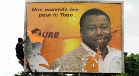 Un togolais déchire une affiche électorale de Faure Gnassingbé, Lomé, avril 2005 REUTERS/Noel Koukou Tadegnon