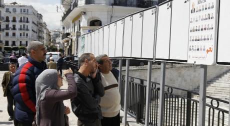 Des Algériens devant une affiche de campagne, avril 2012. © Louafi Larbi / Reuters