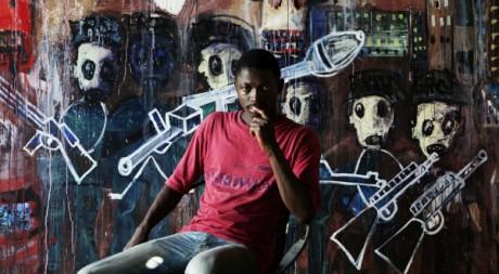 Aboudia, artiste peintre ivoirien pose devant une de ses oeuvres qui évoque la guerre, 29 avril 20111, REUTERS/Finbarr O'Reilly