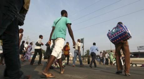 Badauds traversant la rue à Abidjan, 22 décembre 2010, REUTERS/Luc Gnago