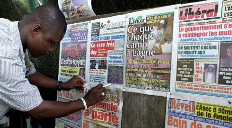 Un vendeur de journaux à Abidjan, novembre 2002. © REUTERS/Luc Gnago