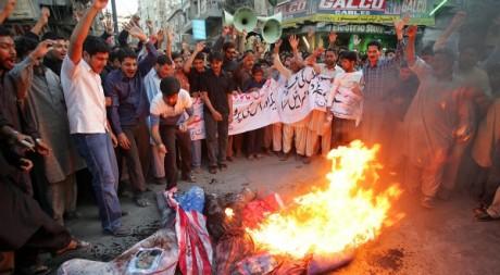 Des chiites qui brûlent un drapeau américain à Karachi, le 11 février 2006.REUTERS/Athar Hussain