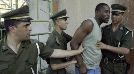 Des gendarmes algériens arrêtent un migrant clandestin à Sidi Driss, le 20 mai 2009. REUTERS/Louafi Larbi