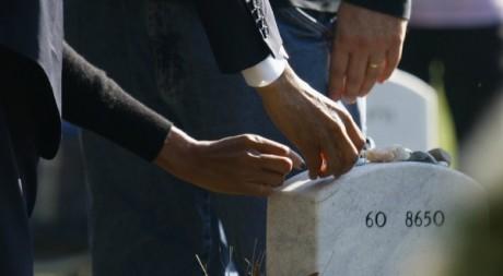 Barack Obama déposant de sa main gauche une pièce sur une pierre tombale. Le 11 novembre 2012. Reuters/Jonathan Ernst