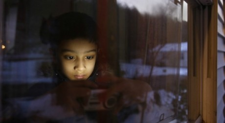 Un garçon de 6 ans qui regarde des vidéos sur son appareil. Le 3 janvier 2013. Reuters/Carlo Allegri
