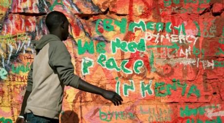 Un Kényan passe devant un graffiti, février 2013. © PHIL MOORE / AFP