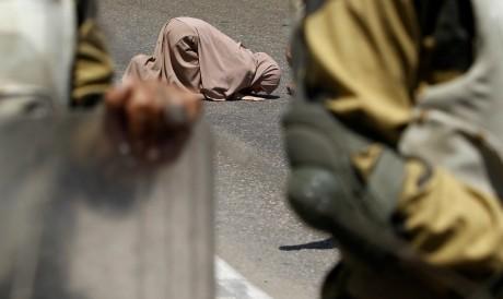 Une partisane des Frères musulmans prie en arrière plan, le 21 juillet 2013.REUTERS/Amr Abdallah Dalsh