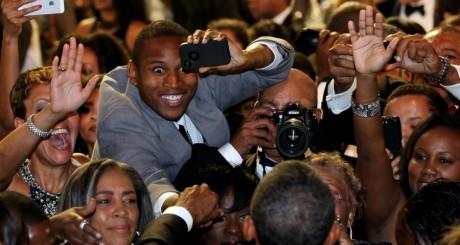 Des Africains-Américains prenant le président Obama en photo / Reuters