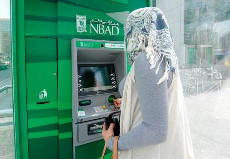 Une femme devant un distributeur de la Banque Nationale d'Abou Dabi, REUTERS/Ben Job