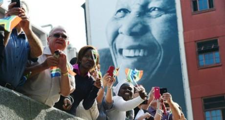 Des Sud-Africains saluant le passage du cortège funèbre de N. Mandela, 11 décembre 2013 / AFP