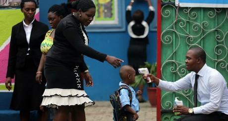 Un responsable de l'école prend la température d'un enfant avant qu'il entre en cours, Lagos, le 22 septembre 2014. REUTERS/Ak