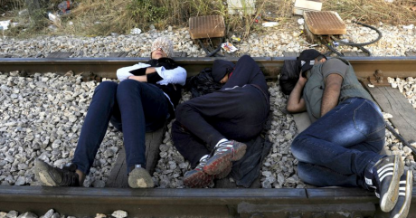 Des migrants se reposent sur les rails près de la frontière gréco-macédonienne, le 21 août 2015. REUTERS/Alexandros Avramidis