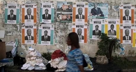 Une femme passe devant des affiches de campagne de candidats à Abidjan, le 21 octobre 2015. REUTERS/Luc Gnago