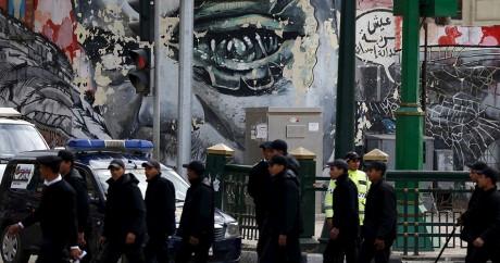 Des policiers devant un grafiti à proximité de la place Tahrir au Caire, le January 25, 2016