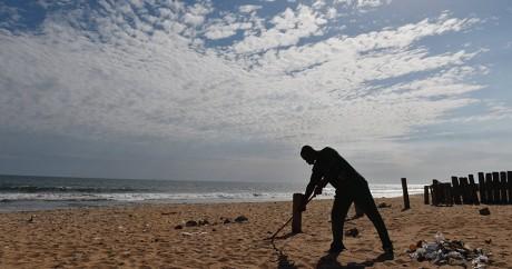 Un homme ramasse des débris sur la plage de Grand-Bassam, le 15 mars. Crédit photo: ISSOUF SANOGO / AFP