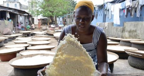 Une femme remue la semoule de manioc pour préparer l'attiéké à Abidjan. ISSOUF SANOGO / AFP