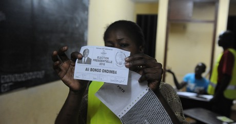 Une membre du comité électoral montre un bulletin pour Ali Bongo dans un bureau de vote de Libreville. STEVE JORDAN / AFP