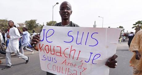 Lors d'une manifestation le 16 janvier 2015, un sénégalais brandit une pancarte au nom des auteurs des attaques  de Paris. AFP