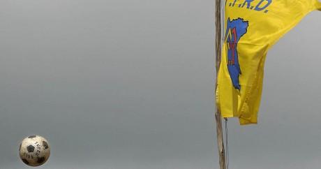 Un ballon de football passe près d'un drapeau à l'effigie de la fédération congolaise de football. AFP