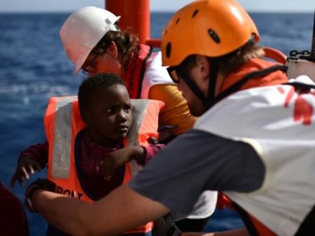Un humanitaire de SOS Méditerranée prend un enfant dans ses bras, le 24 mai 2016. AFP/Gabriel Bouys